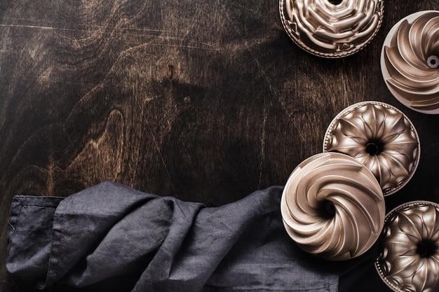 면 주방 냅킨 또는 수건 및 오븐용 접시와 어두운 갈색 나무 질감