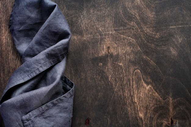 Dark brown wood texture with cotton kitchen napkin or towel over . abstract background.copy space background