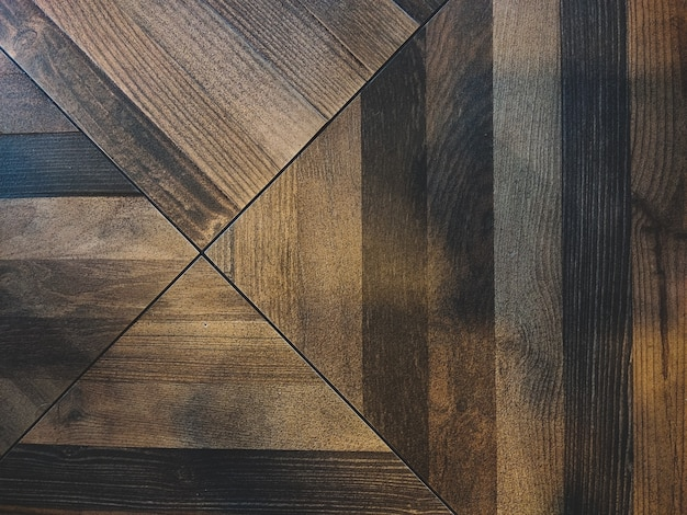 Dark brown wooden parquet floor background with asymmetric intersecting stripes triangles and lines