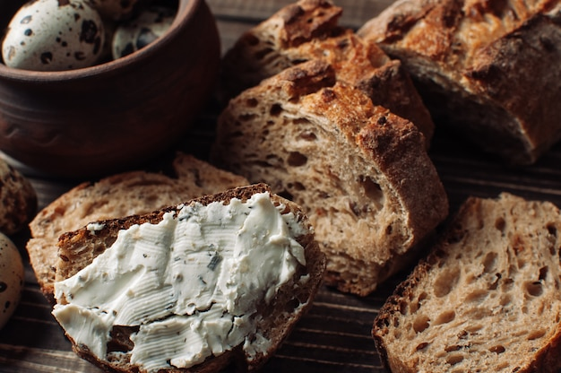 Dark buckwheat bread is spread with cottage cheese with herbs in a cut on a wooden table near quail eggs in a clay plate in a rustic style.