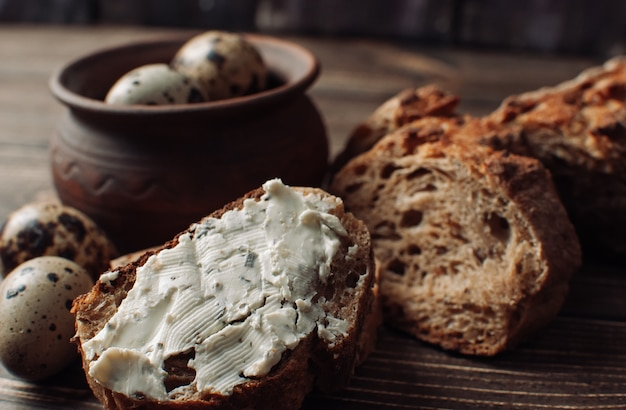 Dark buckwheat bread is spread with cottage cheese with herbs in a cut on a wooden table near quail eggs in a clay plate