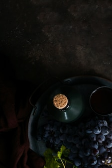 Dark bunch of grape with water drops in low light, red wine, dark photo with copy space