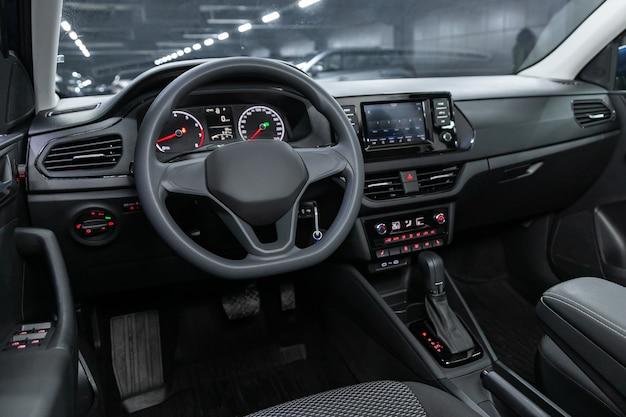 어두운 차 내부-스티어링 휠, 변속 레버 및 대시 보드, 실내 온도 조절기, 속도계, 디스플레이. 새로운 세련된 자동차의 살롱