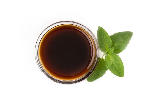 흰색 배경에 분리된 녹색 민트 잎이 있는 다크 카라멜 시럽 또는 간장