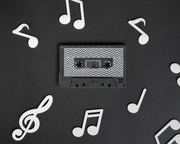 Dark cassette tape with white musical notes surrounding it