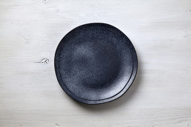 Темная керамическая тарелка на белом деревянном фоне