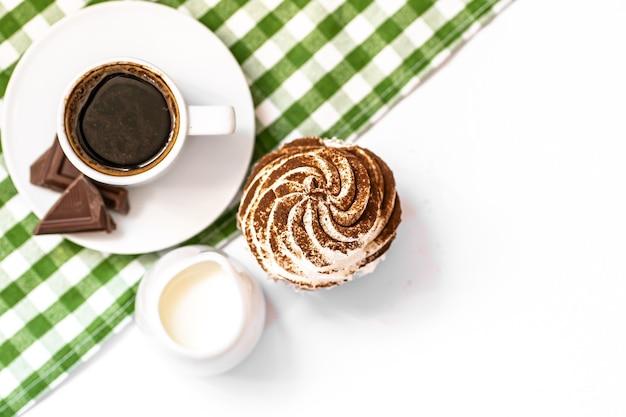 緑のナプキンの上面図にホットブラックコーヒーのカップとダークチョコレートとココアチョコレートのカップケーキ