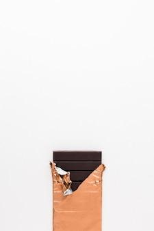 Dark chocolate bar in golden wrapper on white background