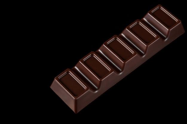 黒の孤立した背景にダークチョコレートバー。甘くて人気の商品。上面図