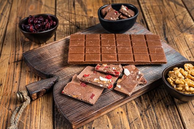Плитка темного шоколада с фундуком, арахисом, клюквой и сублимированной малиной на деревянной доске