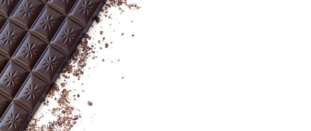 白い表面に分離された削りくずの上面図とダークチョコレートバー