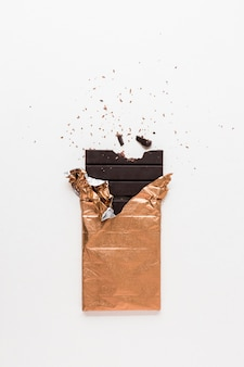 Dark chocolate bar wrapped in golden foil with missing bite on white background