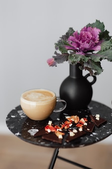 Dark chocolate brittle and milk tea on a black table with an ornamental kale flower