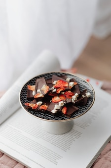 Dark chocolate brittle with dried strawberry in a plate on an opened book