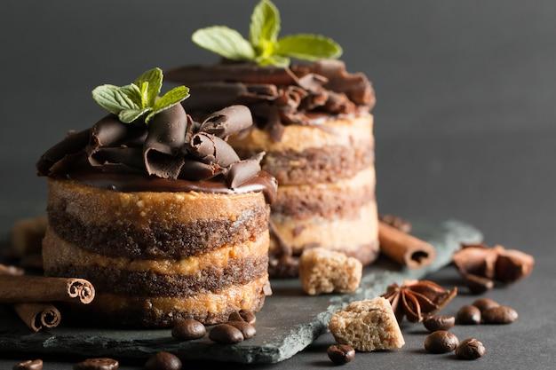 Dark chocolate cakes on black slattern board with mint, cinnamon, coffee beans on a wooden  background. tasty dessert food concept.