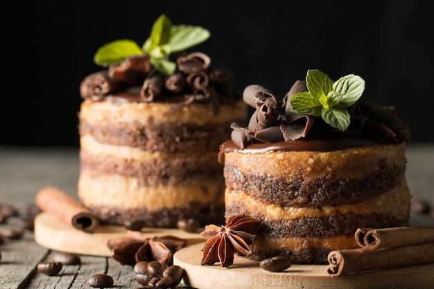 Темные шоколадные торты на черной доске slattern с мятой, корицей, кофейными зернами на деревянной предпосылке. вкусная десертная еда концепция.