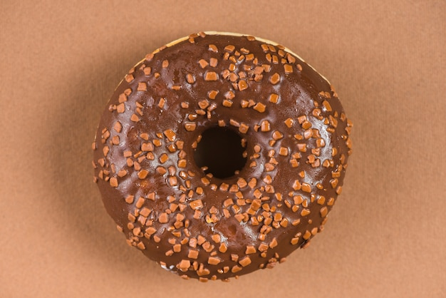 Dark chocolate doughnut with sprinkles on brown background