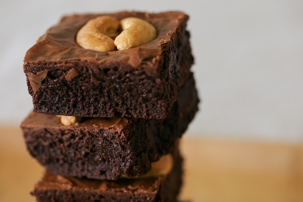 Гайки анакардии отбензинивания темных шоколадных помадок шоколада на деревянной плите с космосом экземпляра. вкус вкусный, горьковато-сладкий, жевательный и нежный. брауни - один из видов шоколадного торта. концепция домашней выпечки