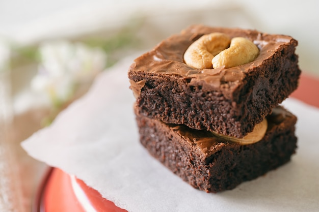 Dark chocolate fudge brownies topping with cashew nuts.