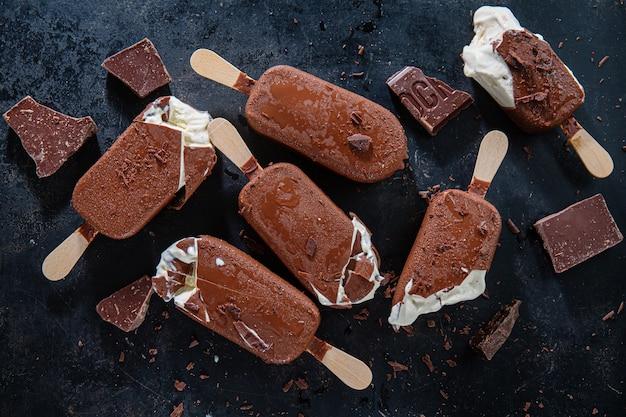 Dark chocolate ice cream popsicles with grated chocolate on dark plate. closeup