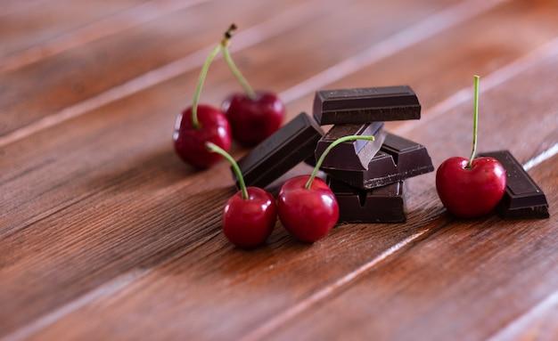 木製の背景に赤いサクランボで隔離のダークチョコレートの部分