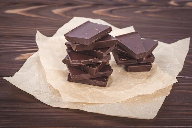 나무 판의 갈색 벽에 다크 초콜릿 조각. 구겨진 공예 종이에 과자, 사탕.