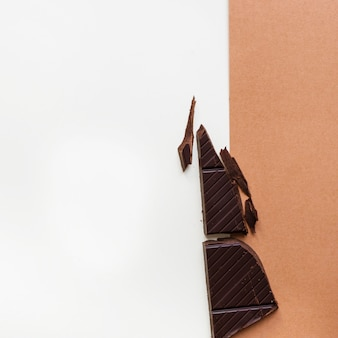 Dark chocolate pieces on white and brown background
