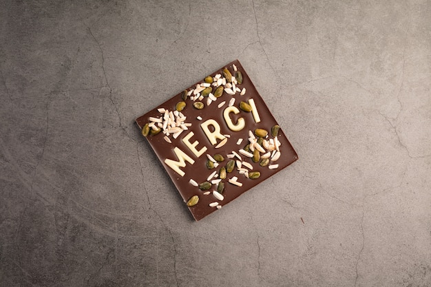 Dark chocolate square with white chocolate thank you note on dark background