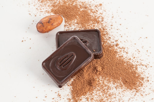 Dark chocolate squares with crushed almonds and cocoa bean on a white background