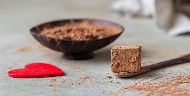 나무 그릇에 코코아 가루와 코코아 가루를 뿌린 다크 초콜릿 트러플.