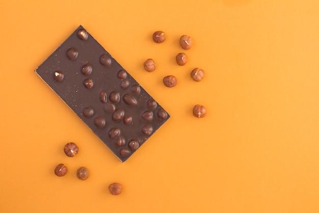 ライトブラウンのテーブルにヘーゼルナッツとダークチョコレート。上面図。スペースをコピーします。