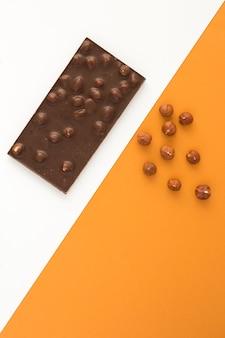 2色の背景にヘーゼルナッツとダークチョコレート。場所は垂直です。上面図。スペースをコピーします。