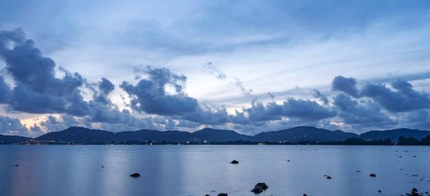 멀리 이동 하는 어두운 구름 물 바다 표면에 반사와 어두운 일몰 구름을 압연 놀라운 보기 풍경 바다입니다.