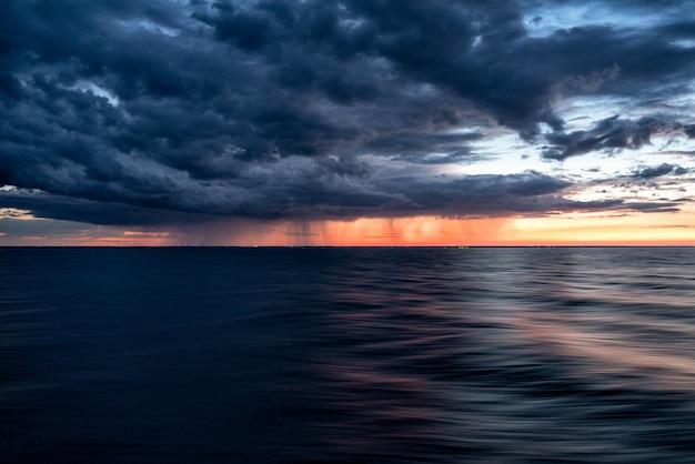 海の暗い水に沈む夕焼け空の暗い雲