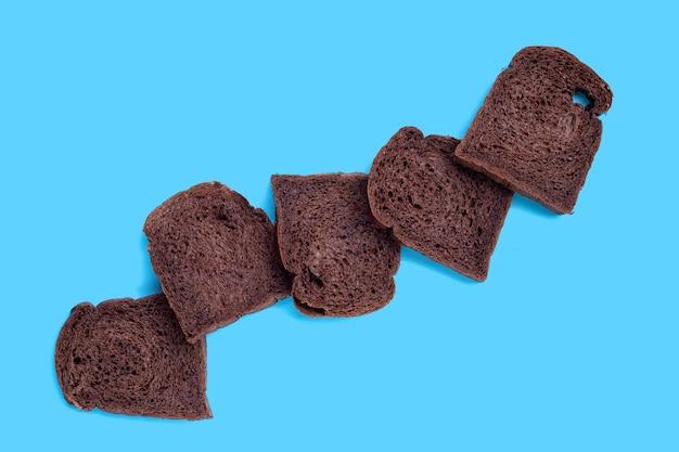 Dark cocoa bread on blue background.