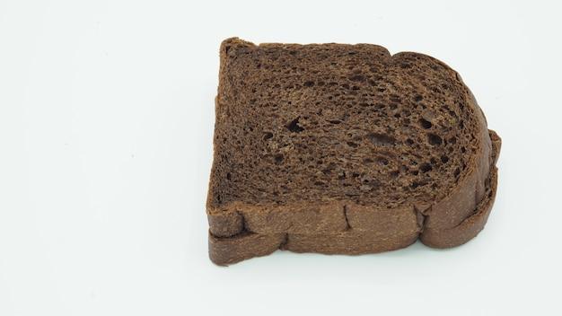 Темный какао-хлеб на белом фоне. это натуральное цельное зерно.