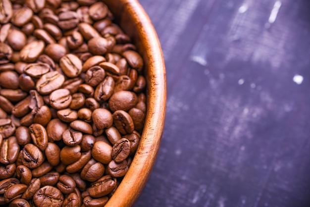 木製カップのダークコーヒー豆。象徴的なイメージ。素朴な木製の背景。閉じる。コピースペース。