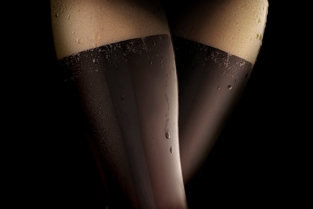 Dark cold beer in two steamed glasses, resembling sexy female legs in black stockings. black background.