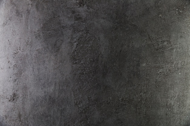Dark concrete wall with coarse surface