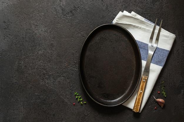 Темный фон приготовления пищи. пустая чугунная тарелка, салфетка и вилка.