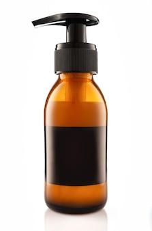 Темная косметическая бутылка из янтарного стекла с дозатором, изолированным на белой стене.