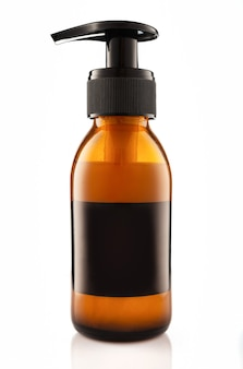 Dark cosmetic amber glass bottle with dispenser isolated on white wall.