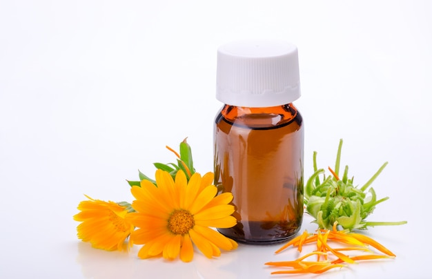 Dark cosmetic bottle of aromatic oil for herbal medicine with calendula flower isolated on white backdrop. marigold extract.