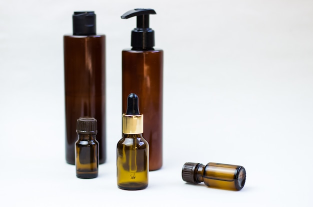Dark cosmetic bottles on a light background