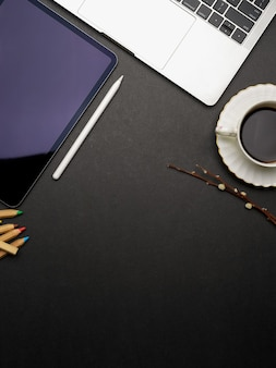 Dark creative flat lay workspace with tablet, laptop, coffee cup and copy space, top view