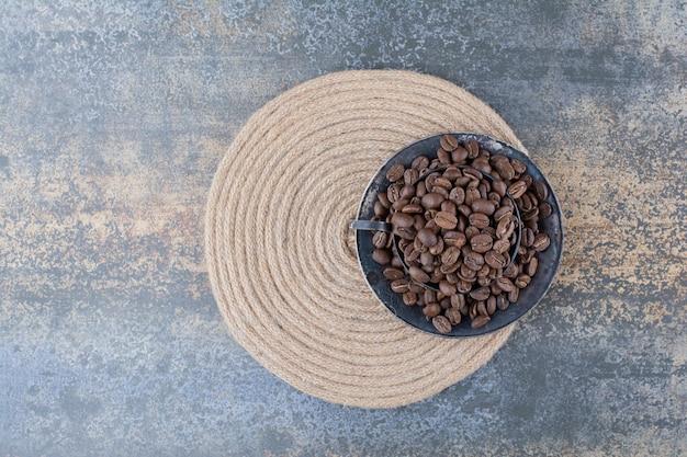 Una tazza scura piena di chicchi di caffè su sfondo marmo. foto di alta qualità