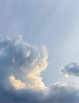 Темные вьющиеся облака на небе, освещенные солнцем