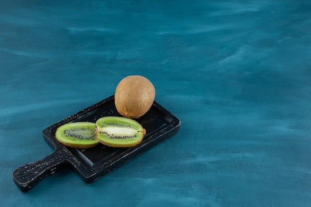 Dark cutting board of fresh kiwi slices on blue surface. Free Photo