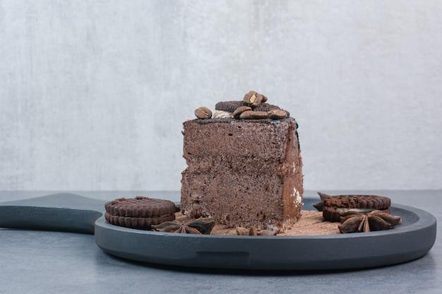 Un tagliere scuro di torta dolce e anice stellato.