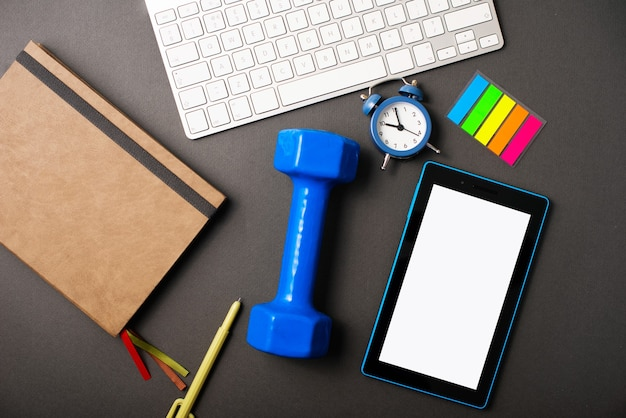 A dark desk with a planner, a blue weight, a tablet, a keyboard for making the time more productive